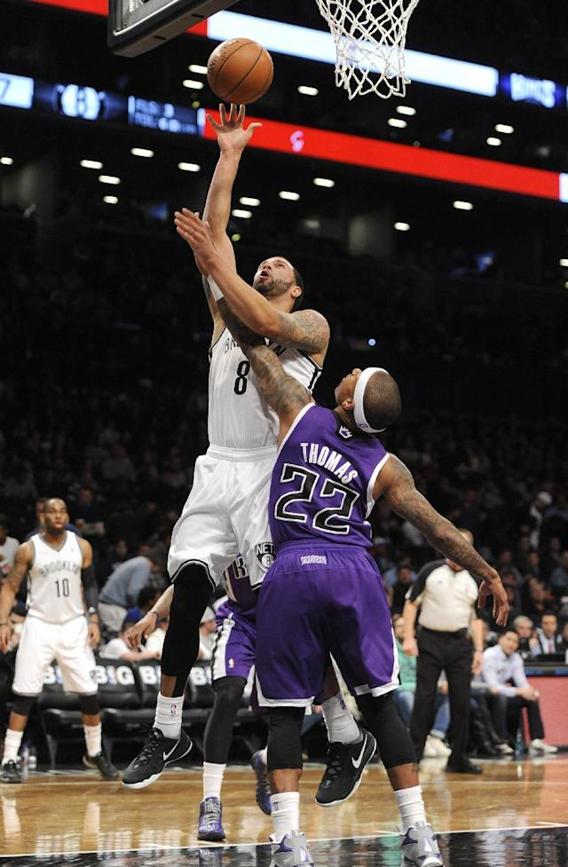 Brooklyn Nets' Deron Williams (8) shoots a basket over Sacramento Kings Isaiah Thomas (22) in the first half of an NBA basketball game on Sunday, March 9, 2014, at Barclays Center in New York. (AP Photo/Kathy Kmonicek)