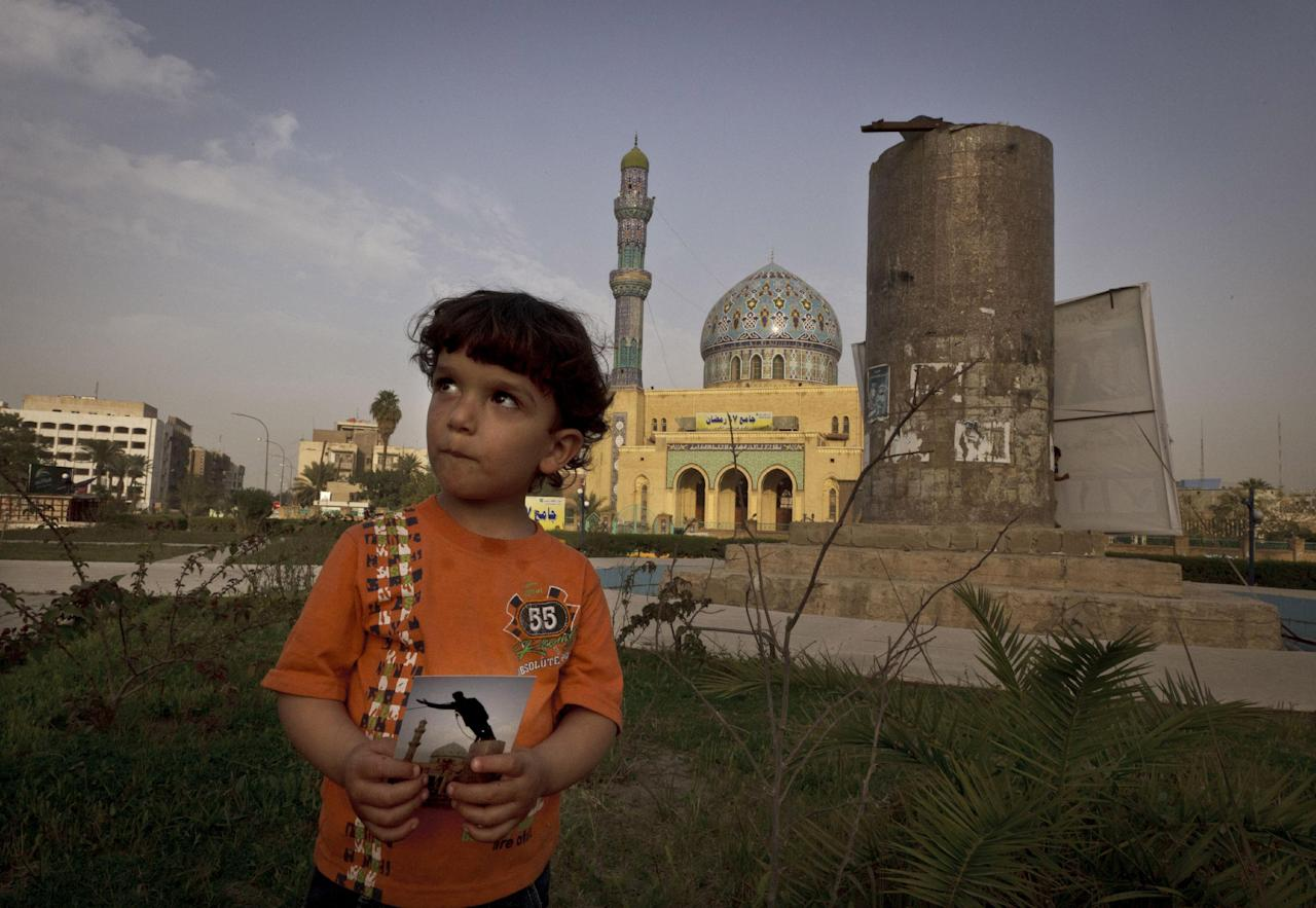 In this Thursday, March 14, 2013 photo, Hussein, 3, poses in Firdous Square in Baghdad with a photograph taken at the site by Jerome Delay of the Associated Press showing the statue of Saddam Hussein being pulled down by U.S. forces and Iraqis on April 9, 2003. Ten years ago on live television, U.S. Marines memorably hauled down a Soviet-style statue of Saddam, symbolically ending his rule. Today, that pedestal in central Baghdad stands empty. Bent iron beams sprout from the top, and posters of anti-American Shiite cleric Muqtada al-Sadr in military fatigues are pasted on the sides. (AP Photo/Maya Alleruzzo)