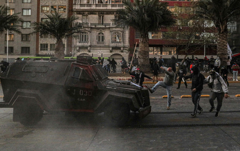 A demonstrator kicks a police armored vehicle during a protest against police in reaction to a video that appears to show an officer pushing a youth off a bridge the previous day at a protest, in Santiago, Chile, Saturday, Oct. 3, 2020. (AP Photo/Esteban Felix)