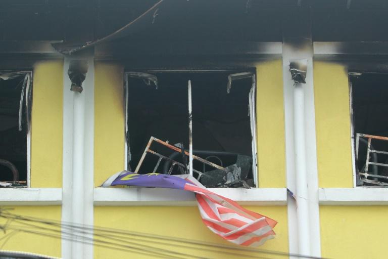 A Malaysian national flag flutters outside burnt windows of the Darul Quran Ittifaqiyah religious school in Kuala Lumpur on September 14, 2017
