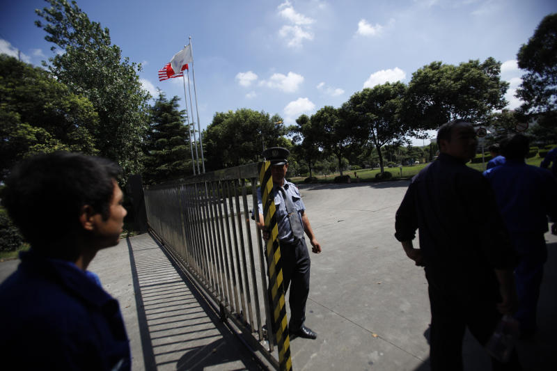 A security guard closes the gate as workers walk in a battery factory nearby Kanghua New Village, Thursday, Sept. 15, 2011 in Shanghai, China. The company said it had suspended lead-related production at the factory as of Sept. 13, at the local government's request, because it had  already used its quota of lead for the year. (AP Photo/Eugene Hoshiko)