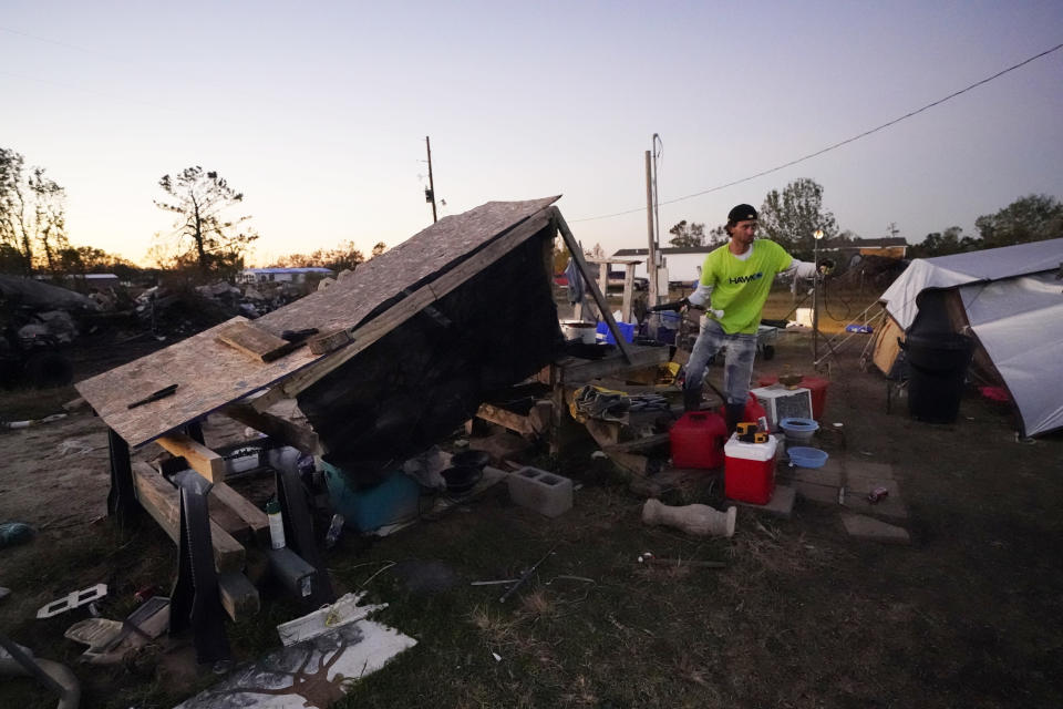 Ricky Trahan runs an extension cord to set up a light, where he now lives in a tent with his wife, in the aftermath of Hurricane Laura and Hurricane Delta, in Lake Charles, La., Friday, Dec. 4, 2020. (AP Photo/Gerald Herbert)