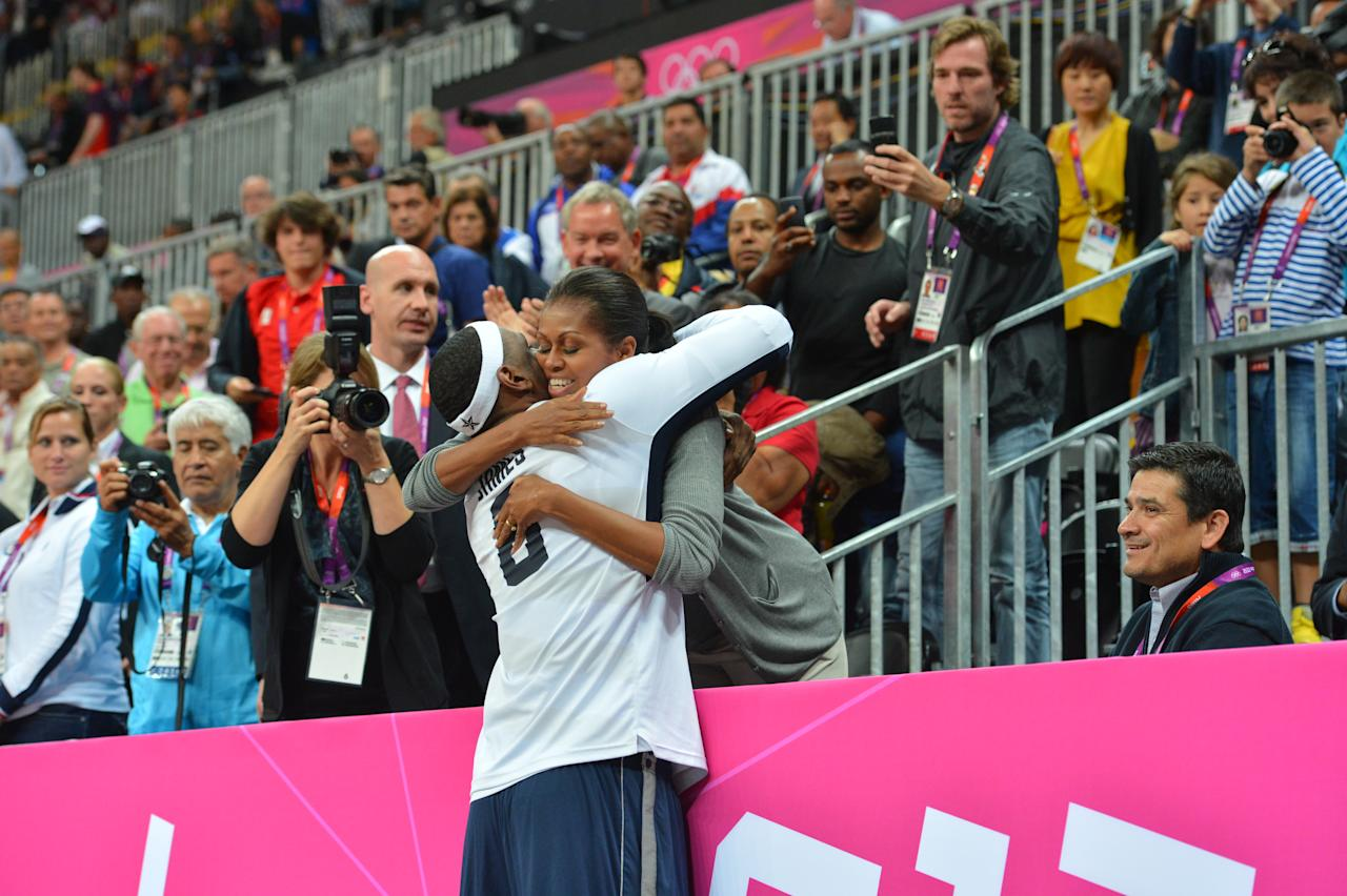 LeBron James #6 of the USA Mens Senior National team hugs The First Lady Michelle Obama after defeating France 98-71 at the Olympic Park Basketball Arena during the London Olympic Games on July 29, 2012 in London, England. NOTE TO USER: User expressly acknowledges and agrees that, by downloading and/or using this Photograph, user is consenting to the terms and conditions of the Getty Images License Agreement. Mandatory Copyright Notice: Copyright 2012 NBAE (Photo by Jesse D. Garrabrant/NBAE via Getty Images)