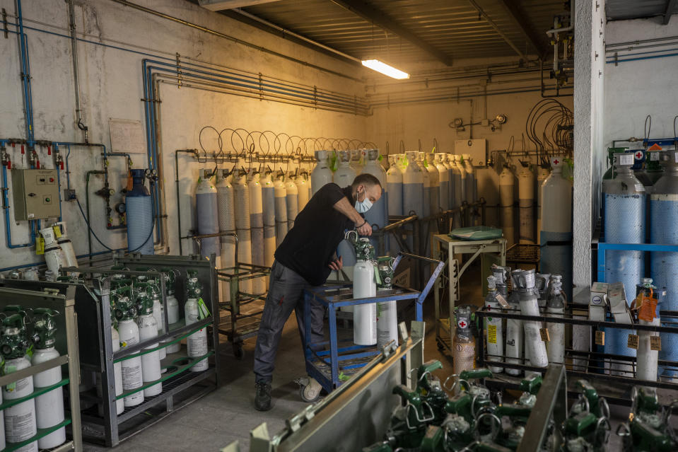 A maintenance worker loads oxygen cylinders in the Severo Ochoa Hospital in Leganes on the outskirts of Madrid, Spain, Wednesday, Feb. 24, 2021. (AP Photo/Bernat Armangue)