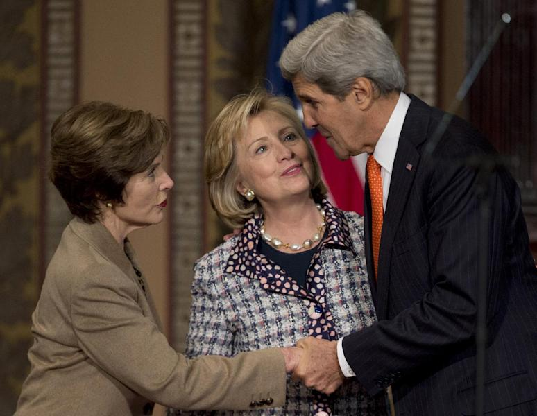 """from left, former first lady Laura Bush, former Secretary of State Hillary Rodham Clinton, and Secretary of State John Kerry greet each other on stage at Gaston Hall Georgetown University in Washington, Friday, Nov. 15, 2013, during the """"Advance Afghan Women"""" symposium. Kerry and his predecessor, Clinton, say Afghanistan is reaching a turning point that will be critical to maintaining advances made by women since the end of Taliban rule. (AP Photo/Carolyn Kaster)"""