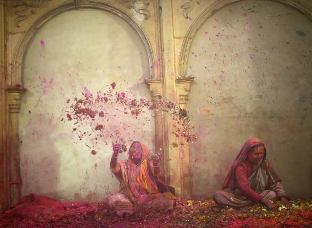 A widow throws flowers into the air during Holi celebrations organised by non-governmental organisation Sulabh International at a widows' ashram in Vrindavan in the northern Indian state of Uttar Pradesh March 14, 2014. Traditionally in Hindu culture, widows are expected to renounce earthly pleasure so they do not celebrate Holi. But women at the shelter for widows, who have been abandoned by their families, celebrated the festival by throwing flowers and coloured powder. Holi, also known as the Festival of Colours, heralds the beginning of spring and is celebrated all over India. REUTERS/Ahmad Masood (INDIA - Tags: ANNIVERSARY RELIGION SOCIETY)
