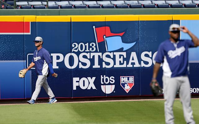 Los Angeles Dodgers manager Don Mattingly walks by a postseason sign during baseball practice Wednesday, Oct. 2, 2013, in Atlanta. The Dodgers are scheduled to face the Atlanta Braves in Game 1 of the NL division series Thursday. (AP Photo/Atlanta Journal Constitution, Jason Getz)