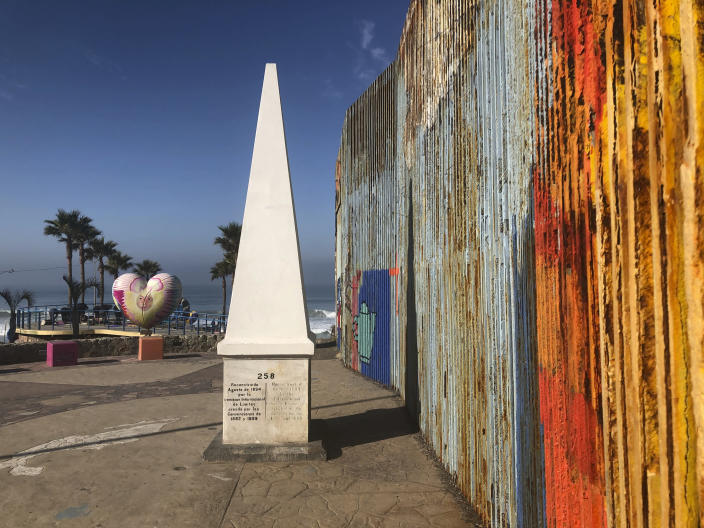 """A white obelisk located on the Mexican side of a border marks the official international line between Mexico and the United States, Saturday, Jan. 25, 2020, in Tijuana, Mexico. The U.S. Border Patrol, reacting to a breach it discovered in a steel-pole border wall believed to be used by smugglers, gave activists no warning this month when it bulldozed the U.S. side of a cross-border garden on an iconic bluff overlooking the Pacific Ocean. On Saturday, after a public apology for """"the unintentional destruction,"""" the agency allowed the activists in a highly restricted area to resurrect the garden. (AP Photo/Elliot Spagat)"""