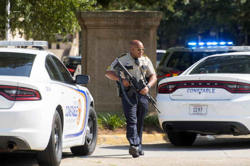 A Baton Rouge City Constable's Office officer with a weapon walks near two LSU police vehicles and Constables Office units parked in between the LSU Student Union and Coates Hall,during investigation of a possible armed intruder in Coates Hall, Tuesday, August 20, 2019.(Travis Spradling/The Advocate via AP)