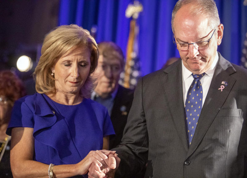 Louisiana Gov. John Bel Edwards and his wife, Donna, hold hands in prayer during his election night watch party in Baton Rouge, La., Saturday, Oct. 12, 2019. (AP Photo/Brett Duke)