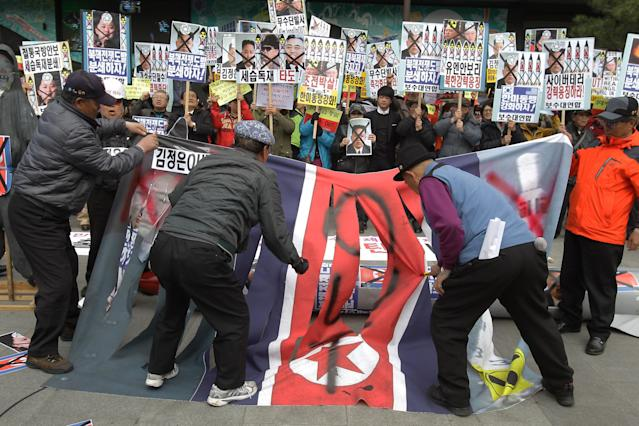 SEOUL, SOUTH KOREA - APRIL 15: South Korean conservative protesters deface a North Korean flag during a rally demonstrating against North Korea on April 15, 2013 in Seoul, South Korea. North Korea marks its founder Kim Il-Sung's 101th birthday today while the fear on possible missile launch continues. (Photo by Chung Sung-Jun/Getty Images)