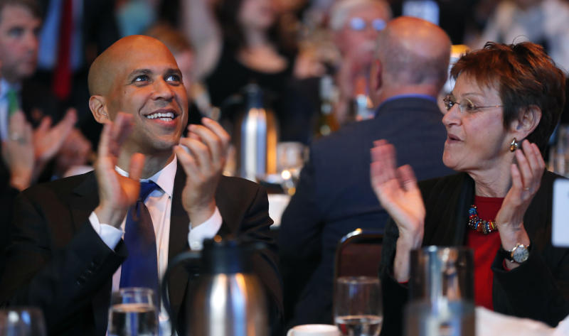 FILE - In this Saturday, Oct. 6, 2018, file photo, U.S. Sen. Cory Booker, D-N.J., sits with former Iowa Lt. Gov. Sally Pederson, right, during the Iowa Democratic Party's annual Fall Gala, in Des Moines, Iowa. Many of the Democratic Party's most ambitious have begun building relationships in the states most responsible for picking the party's next presidential nominee. Booker has raised more than $7 million and campaigned across 21 states for other Democratic candidates this midterm season, according to an aide. (AP Photo/Charlie Neibergall, File)