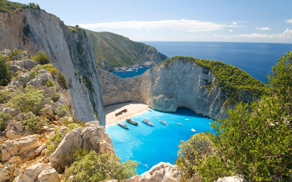 view of blue water and boats from above, big cliffs - David C Tomlinson/ The Image Bank RF