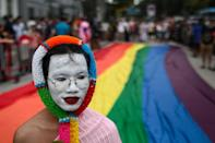 An LGBTQ activist walks past a rainbow banner while taking part in the Pride Parade in Bangkok