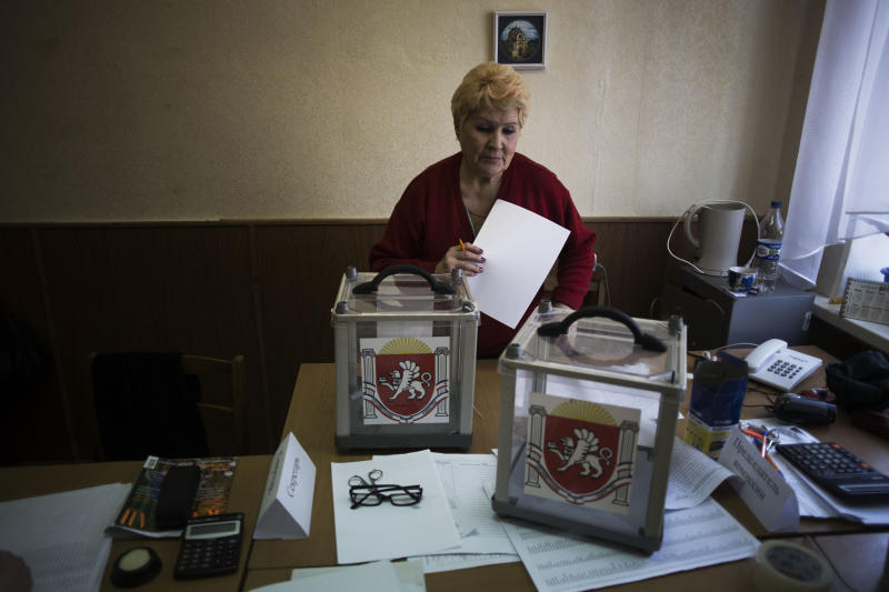 A Ukrainian woman, who is a member of the district electoral committee, makes final preparations as she stands next to ballot boxes for Sunday's referendum at a polling station in Simferopol, Ukraine, Saturday, March 15, 2014. Tensions are high in the Black Sea peninsula of Crimea, where a referendum is to be held Sunday on whether to split off from Ukraine and seek annexation by Russia. (AP Photo/Manu Brabo)