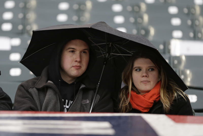 Two fans sit under an umbrella in the rain before a scheduled baseball game between the Cleveland Indians and the New York Yankees, Thursday, April 11, 2013, in Cleveland. The game was delayed due to rain. (AP Photo/Tony Dejak)