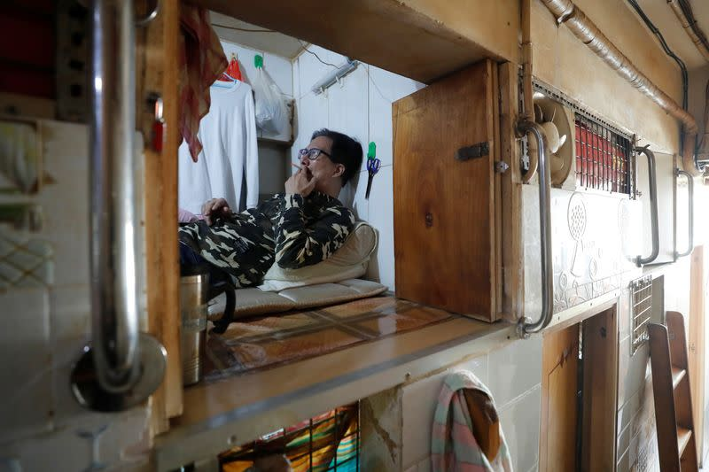 "Simon Wong, 64, smokes a cigarette at his 2 square metre subdivided residential unit, known as a ""coffin home"", following the outbreak of the new coronavirus, in Hong Kong, China February 17, 2020. Picture taken February 17, 2020. REUTERS/Tyrone Siu"