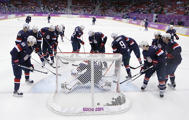 USA players gather around the net before the men's bronze medal ice hockey game against Finland at the 2014 Winter Olympics, Saturday, Feb. 22, 2014, in Sochi, Russia. (AP Photo/David J. Phillip)
