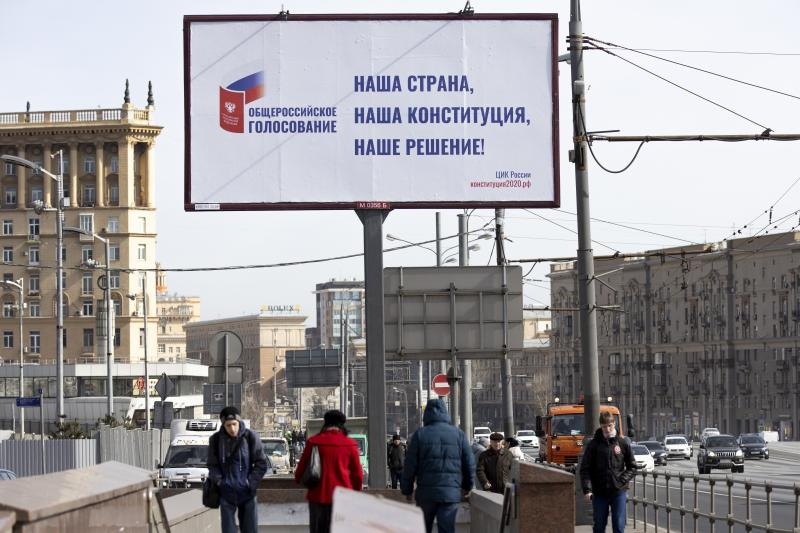 """FILE - In this March 25, 2020, file photo, people walk past a billboard reads """"Our country, our constitution, our decision"""" in a street in Moscow, Russia. Russian President Vladimir Putin is just a step away from bringing about the constitutional changes that would allow him to extend his rule until 2036. The vote that would reset the clock on Putin's tenure in office and allow him to serve two more six-year terms is set to wrap up Wednesday, July 1, 2020. (AP Photo/Alexander Zemlianichenko, File)"""