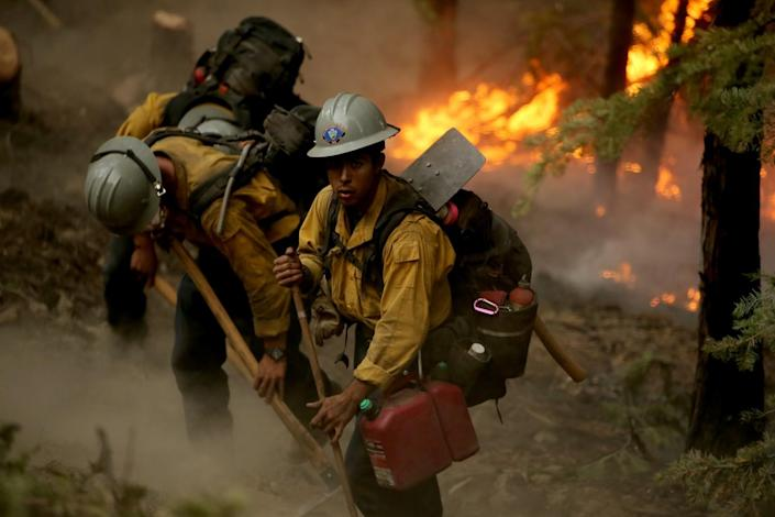 A fire crew at work with flames in the near background.