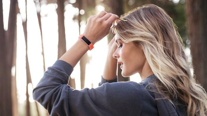 A model in fitness clothing donning an Alta HR fitness tracker on her raised left arm.