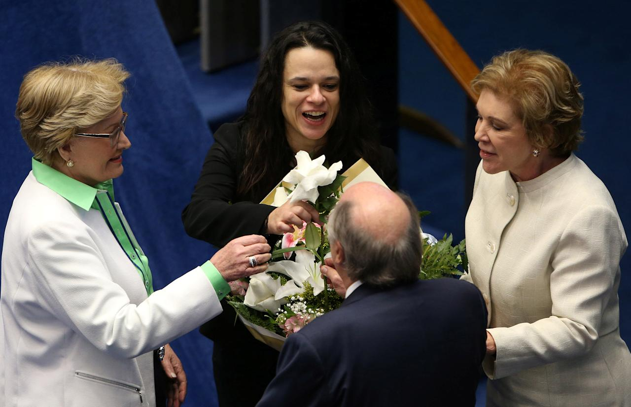 Brazilian jurist Janaina Paschoal (C), co-author of the complaint that originated the impeachment process against suspended president Dilma Rousseff, receives flowers from senators Ana Amelia (L), Marta Suplicy (R) and jurist Miguel Reale Junior during a final session of debate and voting on Rousseff's impeachment trial in Brasilia, Brazil, August 30, 2016. REUTERS/Adriano Machado