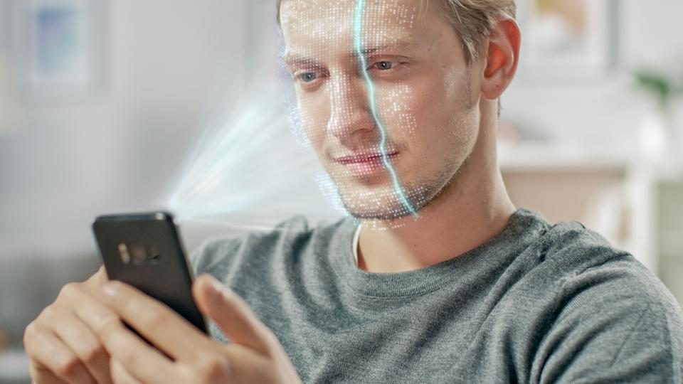 Young Man Identified by Biometric Facial Recognition Scanning Process from His Smartphone. Futuristic Concept: Projector Identifies Individual by Illuminating Face by Dots and Scanning with Laser