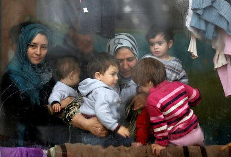 FILE PHOTO: Syrian refugees look through a window inside a refugee centre as they wait for a distribution of humanitarian aid by volunteers of the Bulgarian Red Cross in Sofia, Bulgaria, December 17, 2013. REUTERS/Stoyan Nenov/File Photo