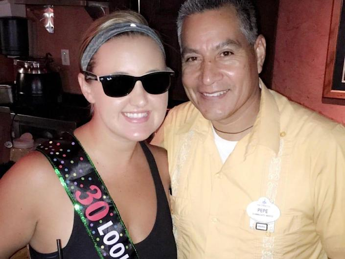 carly in a 30th birthday sash taking a photo with a disney park employee