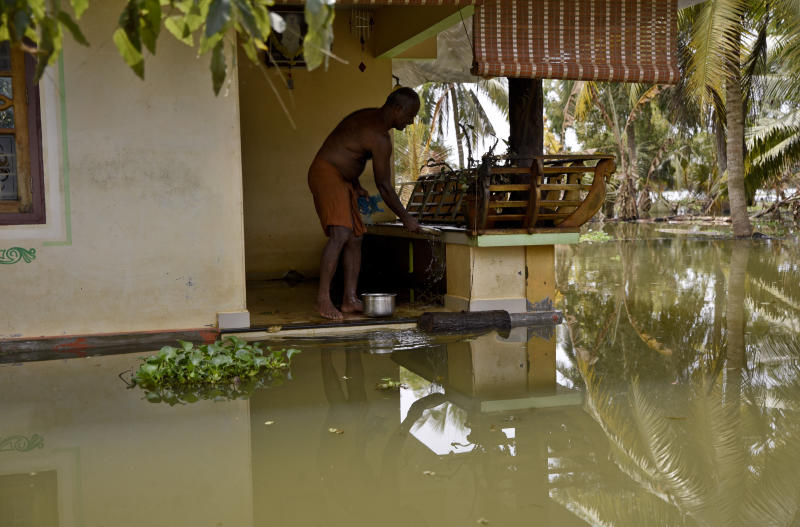 A man stands in his house amid flood waters in Kerala, India — the worst monsoon flooding in a century in the southern Indian state. (ASSOCIATED PRESS)