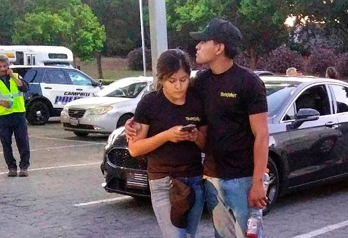 A young couple embrace at a parking lot after a shooting at the Gilroy Garlic Festival on July 28, 2019.