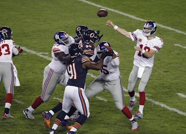 New York Giants quarterback Eli Manning (10) throws a pass which was intercepted by Chicago Bears defensive back Zack Bowman in the first half of an NFL football game, Thursday, Oct. 10, 2013, in Chicago. (AP Photo/Kiichiro Sato)