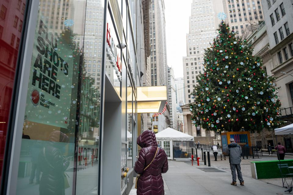 """NEW YORK, NEW YORK - DECEMBER 02: A """"Flu shots are here"""" sign is displayed in the window of a CityMD near a large Christmas Tree displayed in front of the New York Stock Exchange on December 02, 2020 in New York City. (Photo by Alexi Rosenfeld/Getty Images)"""
