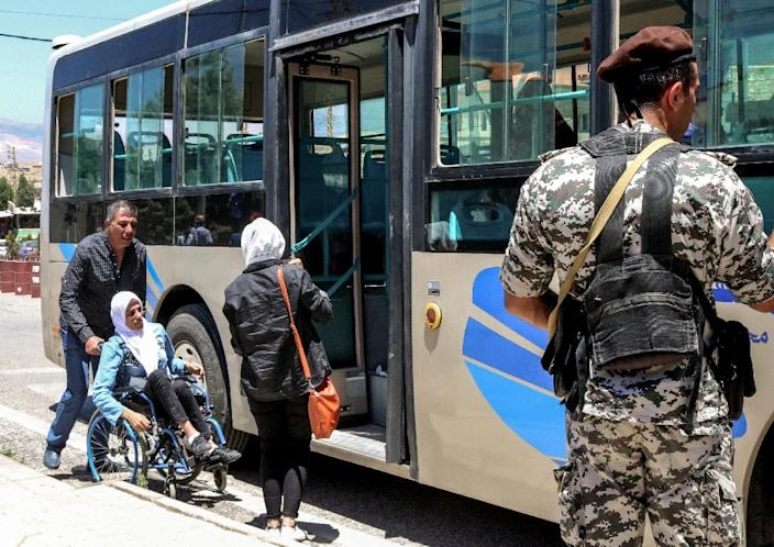 A member of the Lebanese General Security Directorate (R) stands by as a wheelchaired Syrian refugee is helped to board a bus evacuating her from Lebanon at the Masnaa crossing on the Lebanon-Syria border on July 1, 2018 (AFP Photo/HASSAN JARRAH)