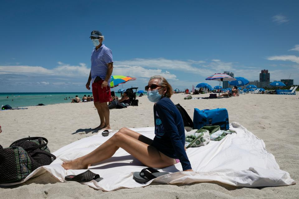 Diane, a nurse from Houston, Texas, sunbathes at the beach next to her husband, both wearing facemasks, in Miami Beach, Florida on June 16, 2020. - Florida is reporting record daily totals of new coronavirus cases, but you'd never know it looking at the Sunshine State's increasingly busy beaches and hotels. (Photo by Eva Marie UZCATEGUI / AFP) (Photo by EVA MARIE UZCATEGUI/AFP via Getty Images)