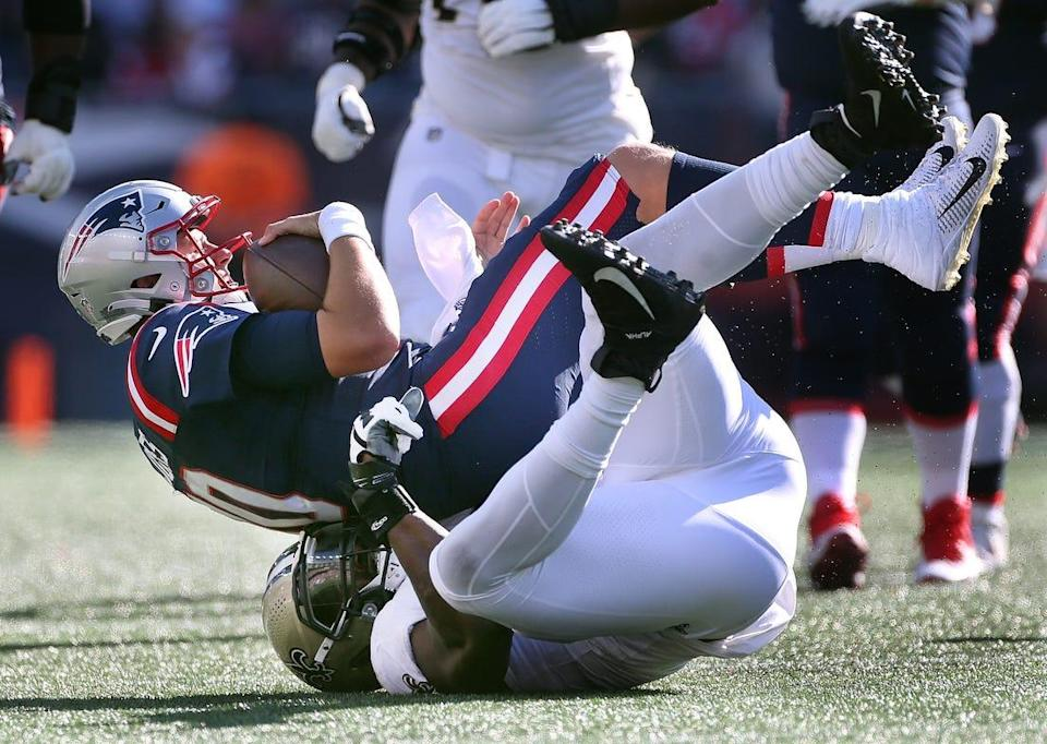 Foxboro, MA  September 26, 2021 -New England Patriots host New Orleans Saints at Gillette Stadium.Patriots QB #10 Mac Jones is sacked by #90 Tanoh Kpassagnon of New Orleans in the 4th quarter.[The Providence Journal/Bob Breidenbach]