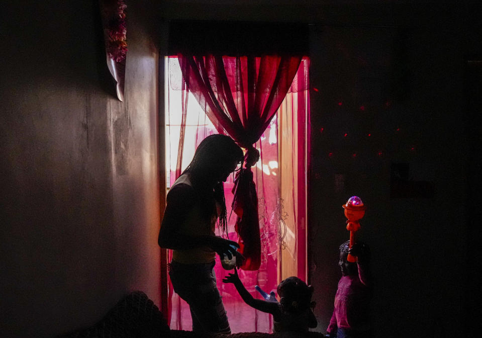 Develine, born to Haitian parents in the Dominican Republic, plays with her Chilean-born sister Cataleya, 2, and neighbor Benita, 3, inside the home of Benita's parents in Santiago's Dignidad camp set up by migrants in Chile, Thursday, Sept. 30, 2021. Many of the wave of Haitians migrants who reached the U.S. border city of Del Rio, Texas in September began their long journey north from Chile, frustrated by the long waits, bureaucratic barriers and rejected applications here. (AP Photo/Esteban Felix)