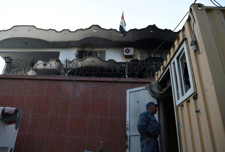 An Afghan security personnel stands at the entrance of the Iraqi embassy building after an attack in Kabul on July 31, 2017