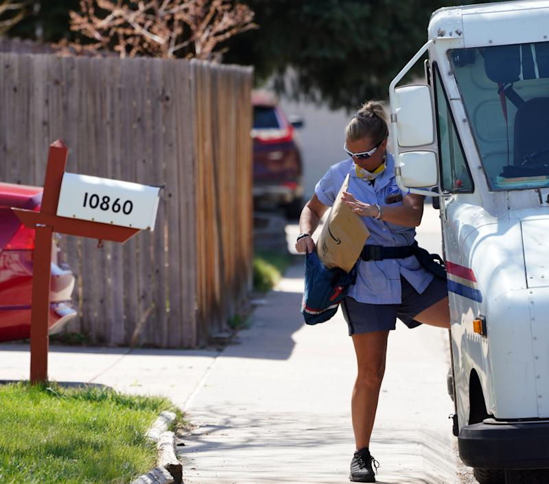 U.S. Postal Service carrier Amy Bezerra loads mail, including an Amazon package, into her delivery pouches along her route in suburban Denver.