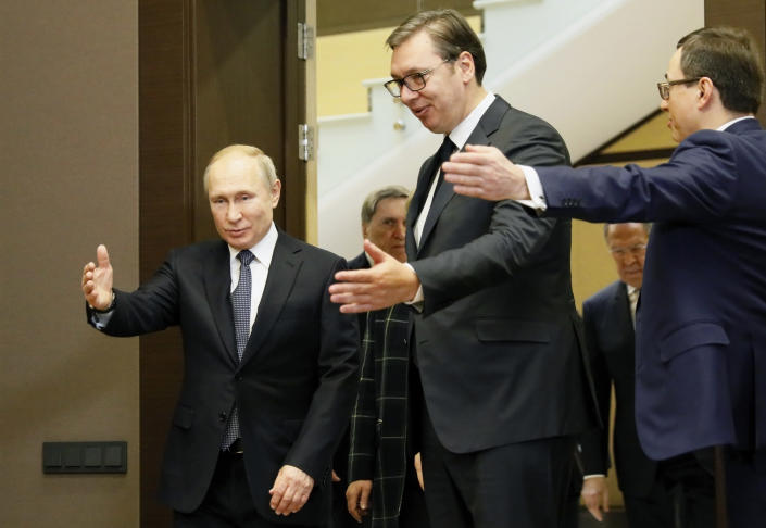 Russian President Vladimir Putin, left, welcomes Serbian President Aleksandar Vucic, center, for the talks during their meeting at the Bocharov Ruchei residence in the Black Sea resort of in Sochi, Russia, Wednesday, Dec. 4, 2019. (Shamil Zhumatov, Pool Photo via AP)