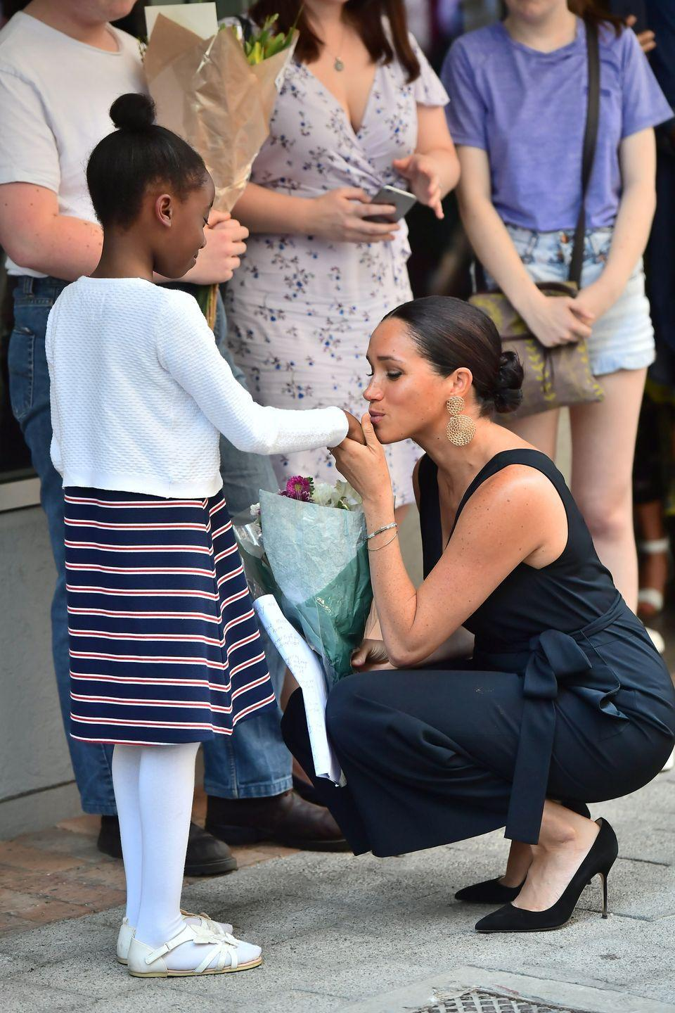 <p>While on tour in South Africa, Meghan kissed a fan's hand when she realized how nervous the little girl was to meet her. Although it was a touching gesture, some thought it broke royal protocol. </p>