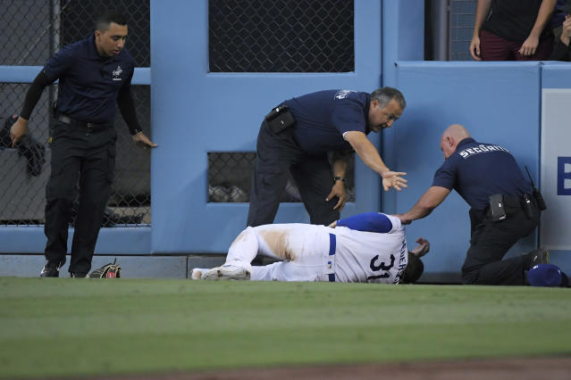 Los Angeles Dodgers right fielder Joc Pederson is attended to by security after colliding with the wall while making a catch on a ball hit by Colorado Rockies' Charlie Blackmon during the fifth inning of a baseball game Monday, Sept. 2, 2019, in Los Angeles. Pederson was taken out of the game after the play. (AP Photo/Mark J. Terrill)