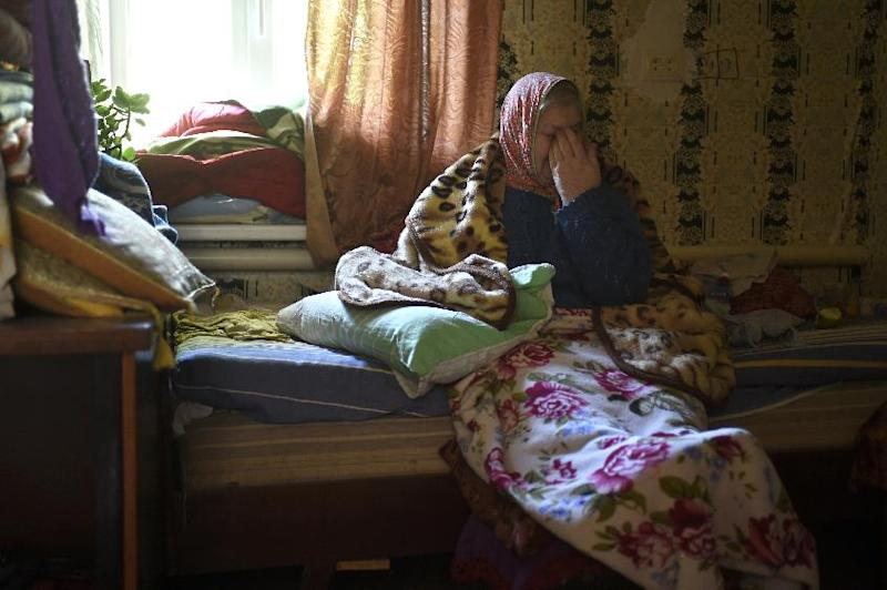 An old woman cries as she sits on a bed in the Oktiabrskiy district of the rebel-held eastern Ukrainian city of Donetsk, on September 19, 2014 (AFP Photo/Philippe Desmazes)