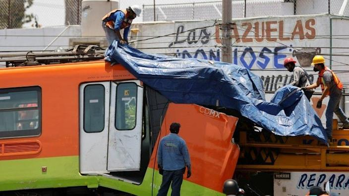 Workers cover a damaged train car after been moved from a site where an overpass for a metro partially collapsed with train cars on it at Olivos station in Mexico City