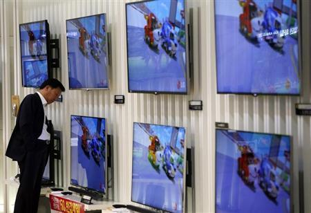 A customer looks at LG Electronics' TV sets which are made with LG Display flat screens at its store in Seoul