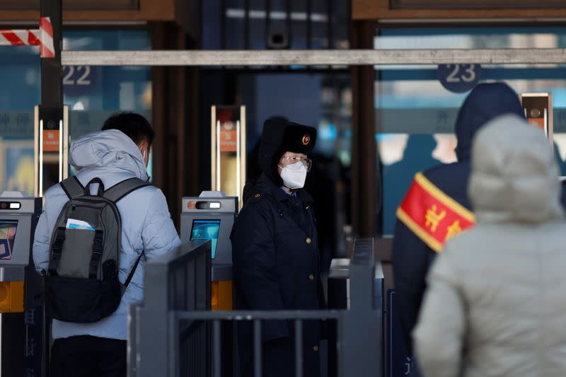 A railway staff member wearing face masks and protective glasses following the coronavirus disease (COVID-19) outbreak stands at an entrance of a railway station as the Spring Festival travel season begins ahead of the Chinese Lunar New Year, in Beijing