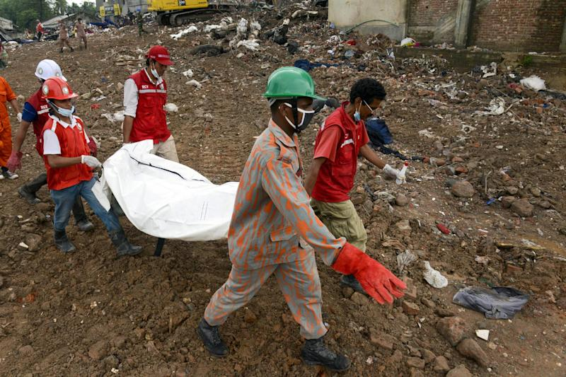 Rescuers carry the body of a victim from the rubble of a building that collapsed in Savar, near Dhaka, Bangladesh, Tuesday, May 7, 2013. Hundreds of survivors of last month's collapse of a building housing garment factories in Bangladesh protested for compensation Tuesday, as the death toll from the country's worst-ever industrial disaster passed 700. (AP Photo/Ismail Ferdous)