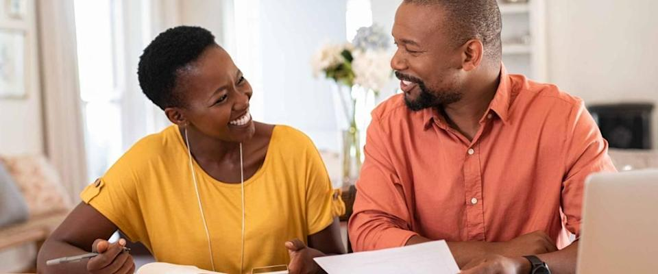Happy looking couple sitting at kitchen table and looking at each other while holding bills