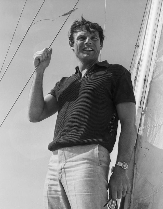 <p>American actor Adam West, of the television series, 'Batman,' stands outdoors on a sailboat, holding a mast line with the wind blowing his hair, circa 1965. (Photo : Hulton Archive/Getty Images) </p>