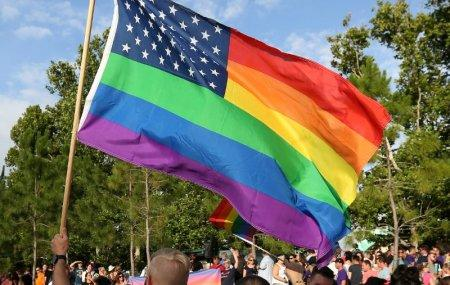 FILE PHOTO - A rainbow U.S. flag is held up during a vigil for the Pulse night club victims in Orlando, Florida, U.S. on June 19, 2016. REUTERS/Carlo Allegri/File Photo
